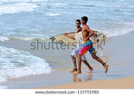 ASHDOD - JUNE 26: Two wave surfers run to the sea on June 26 2011 in Ashdod, Israel.It originated by Polynesian people and was first discovered by Captain Cook in 1778.