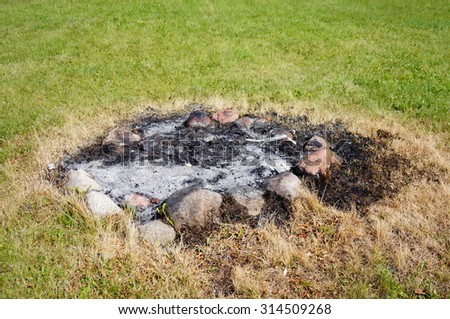 Ashes on a burned fire place on green grass - stock photo