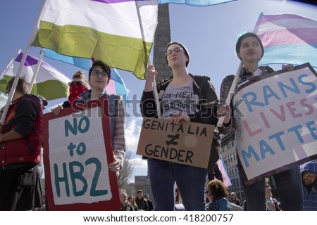 Asheville, North Carolina, USA - April 2, 2016:  People fly symbolic flags and hold signs protesting North Carolina's HB2 law that restricts the rights of those who are transgender