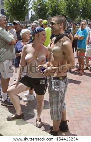 ASHEVILLE, NORTH CAROLINA, USA - AUGUST 25, 2013: A crowd gathers by a topless young woman accompanied by a young man wearing a bra at the Go Topless Rally in downtown Asheville    - stock photo