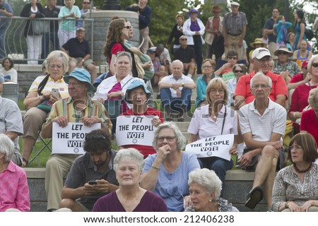 "Asheville, North Carolina, USA - August 4, 2014:  An unhappy crowd of citizens holds political signs that says ""Let the People Vote"" at the 2014 Moral Monday rally on August 4, 2014 in Asheville, NC - stock photo"