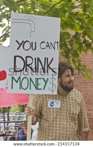 Asheville, North Carolina, USA - August 4, 2014:  Man at a Moral Monday rally holds a sign protesting fracking on August 4, 2014 in downtown Asheville, NC   - stock photo