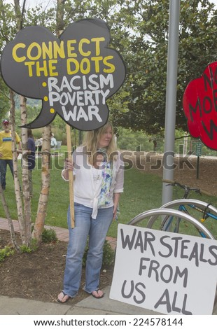 Asheville, North Carolina, USA - August 4, 2014: Moral Monday protesters of all ages hold anti fracking signs and urge people to vote on August 4, 2014 in downtown Asheville, North Carolina - stock photo