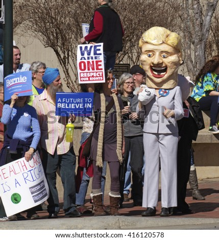 Asheville, North Carolina, USA - February 28, 2016:  Humorous effigy of Hillary Clinton holding a bag of money while Bernie Sanders supporters holding signs confront her at a Bernie Sanders rally
