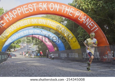 Asheville, North Carolina, USA - July 26, 2014:  A young male runner covered in colorful dye nears the finish line as he races in the 5K Asheville Color Run on July 26, 2014 in downtown Asheville, NC  - stock photo