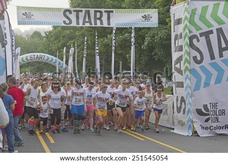 Asheville; North Carolina; USA - July 26; 2014: Color Run Runners wearing colorful t-shirts and headbands burst enthusiastically from the starting line as the race begins in downtown Asheville; NC - stock photo