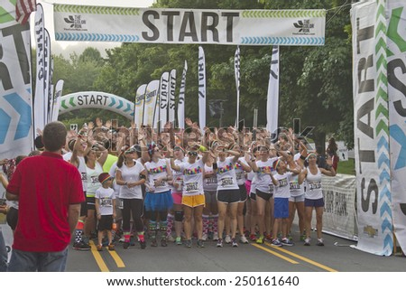 Asheville, North Carolina, USA - July 26, 2014: Excited Color Run Participants wait impatiently at the starting line for the race to begin on July 26, 2014 in downtown Asheville, NC  - stock photo