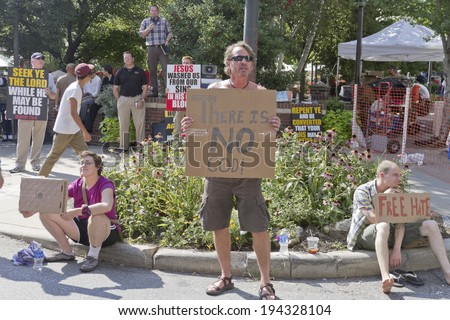Asheville, North Carolina, USA - July 26, 2013: People hold opposing Christian and Atheist signs at the Bele Chere Street Festival on July 26, 2013 in downtown Asheville, North Carolina  - stock photo