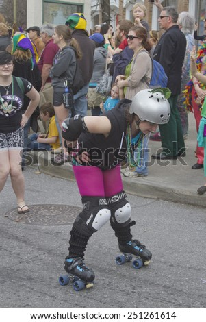 Asheville, North Carolina, USA - March 2, 2014: A female skater wearing athletic gear and Mardi Gras beads bends over as she skates by happy spectators in the annual Mardi Gras Parade  - stock photo
