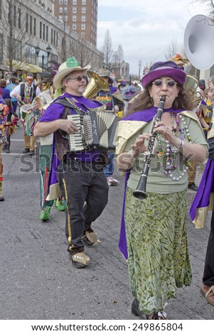 Asheville; North Carolina; USA - March 2; 2014; Band musicians wearing whimsical costumes play music as they march in the annual Mardi Gras Parade on March 2; 2014 in downtown Asheville; NC  - stock photo