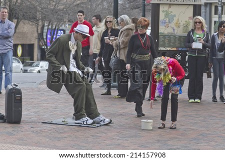 Asheville, North Carolina, USA - March 2, 2014: Living statue street artist ans back at an impossible angle as a woman bends over to give him a tip on March 2, 2014 in downtown Asheville, NC  - stock photo