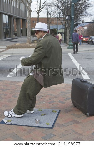 Asheville, North Carolina, USA - March 2, 2014: Male living statue performer in a suit appears blown backward at an impossible angle while remaining immobile on March 2, 2014 in Asheville, NC
