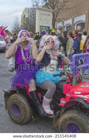 Asheville, North Carolina, USA - March 2, 2014:  People in colorful costumes blow kisses and give pageant style waves to appreciative spectators in the Mardi Gras parade in downtown Ashevile, NC   - stock photo