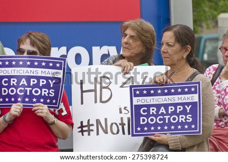 Asheville, North Carolina, USA - May 4, 2015:  Older women hold signs protesting North Carolina's abortion Bill #465 which increases restrictions for women seeking abortions - stock photo