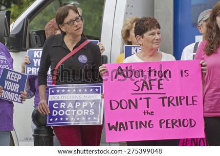 Asheville, North Carolina, USA - May 4, 2015:  Women hold signs protesting North Carolina's abortion Bill #465 which increases restrictions for women seeking abortions