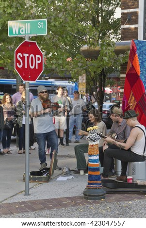 Asheville, North Carolina, USA - November 6, 2015: Street musicians play for tips and a crowd of onlookers by the Flat Iron statue and a colorful knit covered pole on Wall St. in downtown Asheville