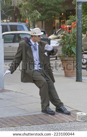 Asheville, North Carolina, USA - September 26, 2014:  A man makes tips as a living statue leaning at an impossible angle as if he is blown back by the wind on September 26, 2014 in downtown Asheville - stock photo