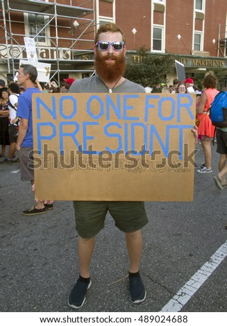 "Asheville, North Carolina, USA: September 12, 2016: A young, male protester holds a sign at a Donald Trump Rally saying ""No One For President"" on September 12, 2016 in downtown Asheville, NC"