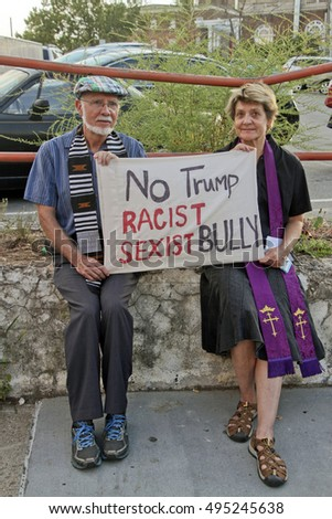 "Asheville, North Carolina, USA: September 12, 2016: Man and a woman wearing a Christian vestment hold protest sign at a Donald Trump campaign rally saying  ""No Trump Racist Sexist Bully."""