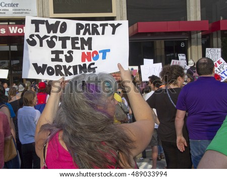 "Asheville, North Carolina, USA: September 12, 2016: Woman at a Donald Trump campaign rally holds a sign saying ""Two Party System Is Not Working"" on September 12, 2016 in downtown Asheville, NC"