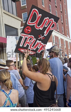 "Asheville, North Carolina, USA: September 12, 2016: Woman protester amid a crowd at a Donald Trump campaign rally holds sign saying  ""Dump Trump"" on September 12, 2016 in downtown Asheville, NC"