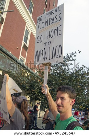 "Asheville, North Carolina, USA: September 12, 2016: Young male protester holds a sign at a Donald Trump campaign rally saying  ""No Moral Compass, Go Home to Mara Lago,"""