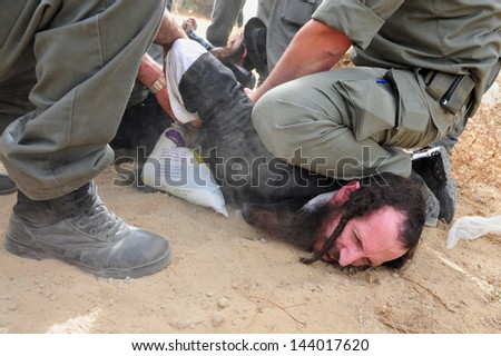 ASHKELON, ISR - MAY 16:Israeli police forces aressting Jewish orthodox man during protest on May 16 2010. It's Israel Police special patrol unit dedicated for crowd control and special operations. - stock photo