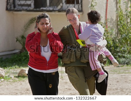 ASHKELON, ISRAEL - JANUARY 10: An unidentified Israeli soldier from rescue team evacuates a couple of young unidentified  girls who was witness of missile explosion launched by Hamas terrorists from Gaza in Ashkelon, Israel on January 10, 2009.