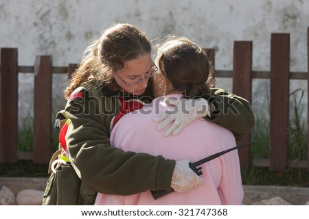 ASHKELON, ISRAEL - JANUARY 10, 2009: israeli soldier from the rescue team hugs young girl who was witness of missile launched by Hamas terrorists from Gaza explode near her house in Ashkelon. - stock photo
