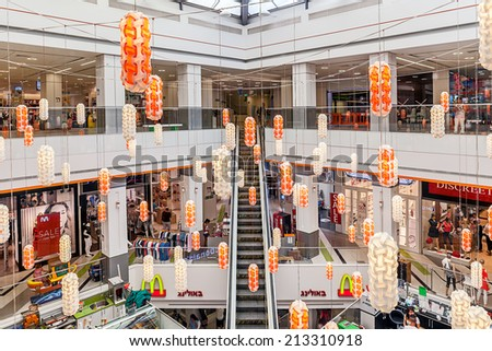 ASHKELON, ISRAEL - JULY 16, 2014: Interior view of Hutzot shopping mall - owned by Aspen Group, offers variety of services like entertainment venues, brand shops, bars, restaurants and movie theater. - stock photo
