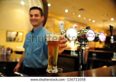 ASHKELON - JULY 27:Bartender pours a glass of beer on July 27 2009 in Ashkelon, Israel.Beer is the oldest alchoholic beverage and has been around since at least the ancient Sumerians of 2600 B.C - stock photo