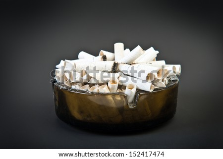 ashtray and cigarettes on black background  - stock photo