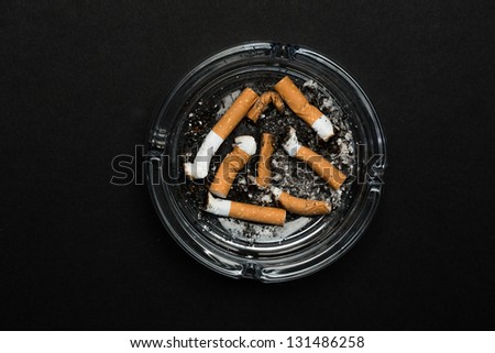 Ashtray full of butts on black background - stock photo