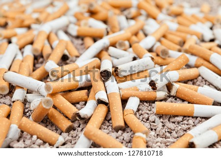 Ashtray full of fallen smoked cigarettes in the sand - stock photo