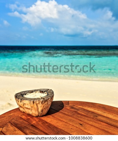 Ashtray with coral sand is on a beach table