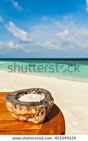 Ashtray with coral sand is on a beach table - stock photo