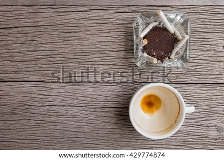 Ashtrays with cigarette smoke and Coffee drinking out Coffee cup with coffee stains ,Top view - stock photo
