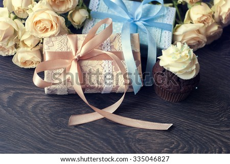 Ashy roses, packed gifts and chocolate cupcake with sprinkles and blue cream on dark table.