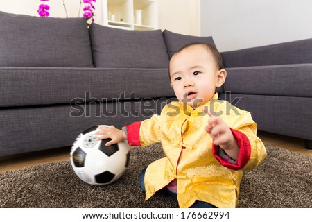 Asia baby boy play soccer ball at home - stock photo