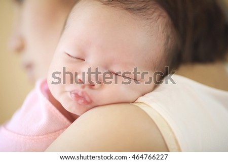 Asia baby sleeping in a warm embrace of mother.