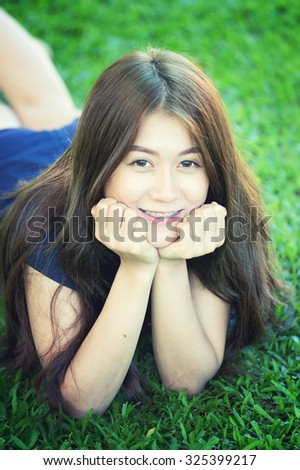 asia beautiful smiling woman lying on grass outdoor. She is absolutely happy.