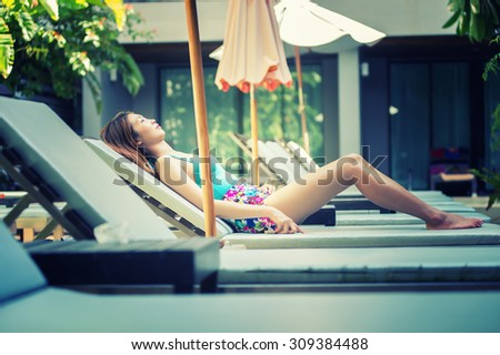 Asia beautiful woman relaxing on lounger near swimming pool in hotel, krabi, Thailand - stock photo