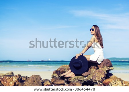 Asia beautiful woman Were sitting Relax On the rocks Blue sky and sea Background - stock photo