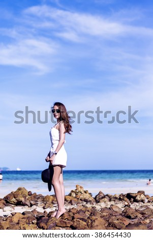 Asia beautiful woman Were stand Relax On the rocks Blue sky and sea Background - stock photo