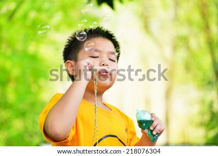 Asia boy blow bubbles at the park - stock photo