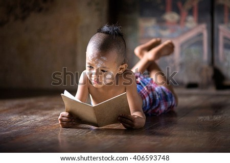 Asia boy reading a book ,sleep on bed wood with traditional Thai suit in Ayutthaya Thailand - stock photo