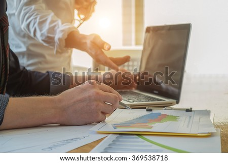 Asia business people discussing the charts and graphs showing the results of their successful teamwork with laptop in morning light. - stock photo