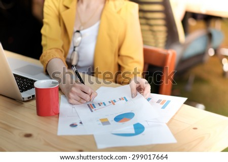 Asia business woman analyzing investment charts with laptop on wood desk. - stock photo
