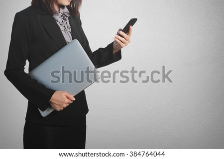 Asia Business woman holding laptop and use phone at concrete wall background.Copy space.