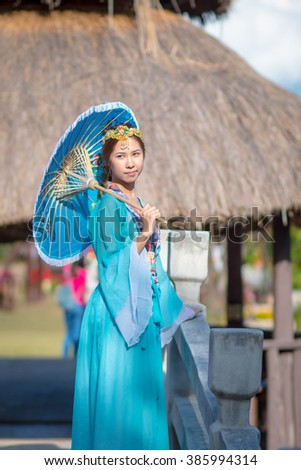 Asia, Chinese beautiful girl in blue traditional dress, classical costumes with umbrella - stock photo